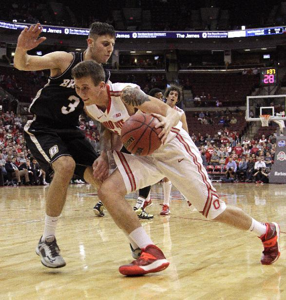 Ohio State's Jake Lorbach, right, drives to the basket against Bryant's Bosko Kostur during the second half of an NCAA college basketball game Wednesday, Dec. 11, 2013, in Columbus, Ohio. Ohio