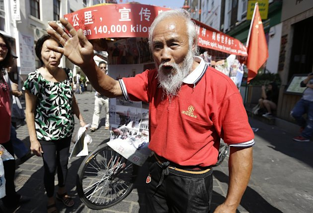 Chinese farmer Chen Guanming smiles as he talks to tourists after he claimed to have made a two-year 87,000 mile journey on a rickshaw from China to come to Britain for the 2012 Summer Olympics, Thursday July 26, 2012, in London. (AP Photo/Alastair Grant)