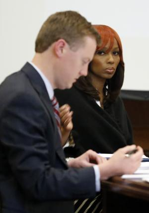 Natasha Stewart, also known as Pebbelz Da Model, looks toward reporters while Jared Tomlinson, one of her attorneys, works on jury instructions in county court in Jackson, Miss., Friday, Jan. 31, 2014. Stewart is charged with depraved-heart murder in the death of 37-year-old Karima Gordon, of Atlanta. She allegedly helped arrange the unlicensed buttocks injections that prosecutors say killed Gordon in 2012. The jury begun deliberations Friday afternoon. (AP Photo/Rogelio V. Solis)