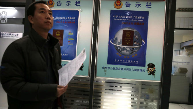A Chinese man walks past billboards announcing a new Chinese passport issued in May this year at a passport office in Beijing, China, Friday, Nov. 23, 2012. The Philippines has protested China's depiction of its claims over the entire South China Sea in an image of a map printed on newly issued Chinese e-passports. (AP Photo/Ng Han Guan)