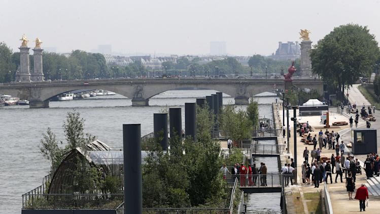 People stroll along the Left Bank of the Seine river where a new promenade has been inaugurated, Wednesday, June 19, 2013 in Paris. The 2.3 km (1.4 miles) walkway offers gardens, cafes, culture and sports activities. (AP Photo/Jacques Brinon)
