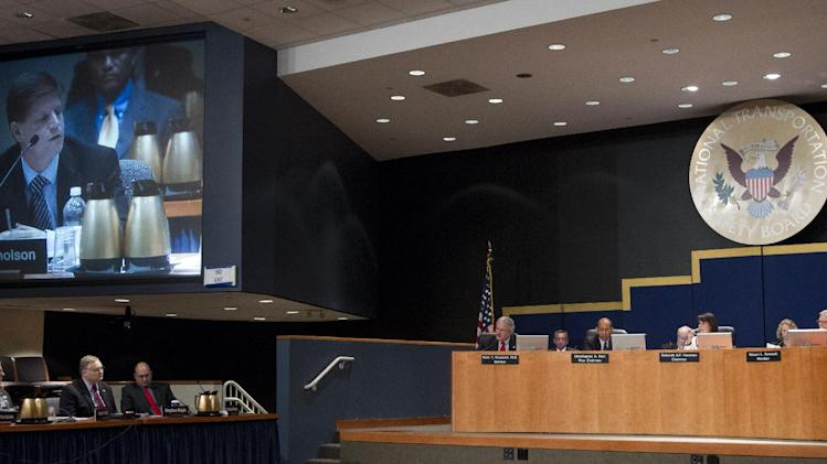 National Transportation Safety Board (NTSB) Investigator-In-Charge Matt Nicholson is projected on a monitor as he testify during a NTSB meeting in Washington Tuesday, July 10, 2012, presided by NTSB Chair Deborah Hersman, center right panel, to determine a cause of a pipeline rupture in 2010 that dumped more than 800,000 gallons of oil into a southwestern Michigan river.  (AP Photo/Manuel Balce Ceneta)