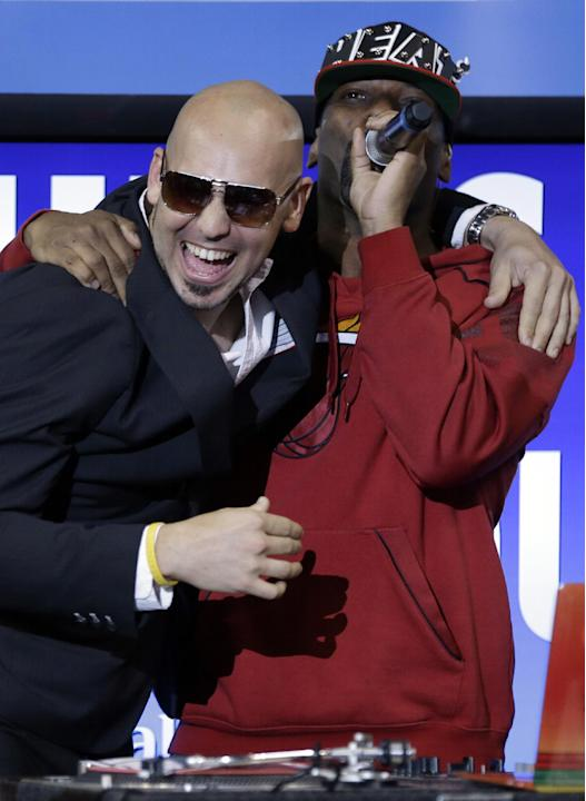 Rapper Pitbull, left, hugs DJ Irie, right, during an NBA basketball game between the Miami Heat and Indiana Pacers, Wednesday, Dec. 18, 2013, in Miami