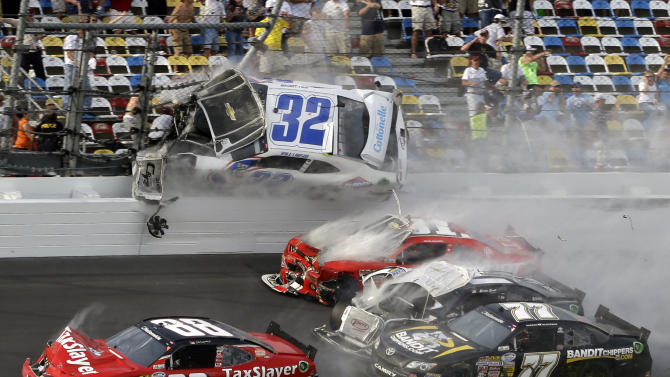 Kyle Larson (32) goes airborne into the catch fence in a multi-car crash including Dale Earnhardt Jr. (88), Parker Kligerman (77), Justin Allgaier (31) and Brian Scott (2) during the final lap of  the NASCAR Nationwide Series auto race at Daytona International Speedway, Saturday, Feb. 23, 2013, in Daytona Beach, Fla. (AP Photo/John Raoux)