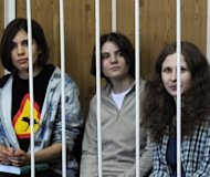 Members of the all-girl punk band &quot;Pussy Riot&quot; Nadezhda Tolokonnikova (left), Yekaterina Samutsevich (centre) and Maria Alyokhina sit behind bars during a court hearing in Moscow on July 23. Members of the all women punk group &#39;Pussy Riot&#39; who allegedly stormed a Moscow church to sing an anti-Putin song face up to seven years in a prison colony after being charged with hooliganism