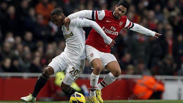 Arsenal's Mikel Arteta (R) challenges Swansea's Jonathan De Guzman during their English Premier League match at the Emirates