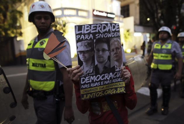 University student holds a poster in front of military police during a protest against Sao Paulo State Governor Alckmin, in Sao Paulo