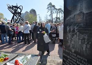 An elderly woman pays her respects to the victims of…