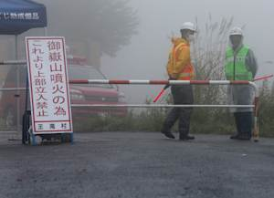 Security workers stand by a closed road approaching…