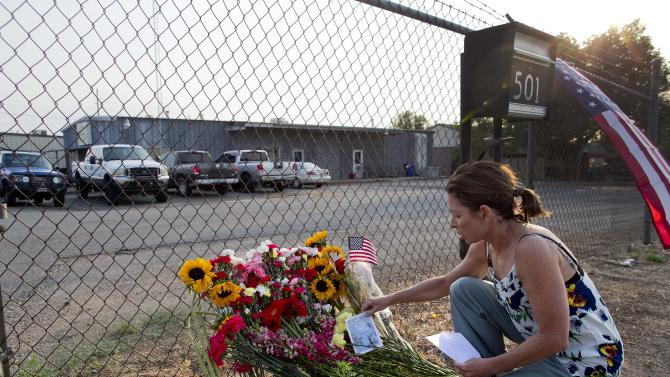 Toby Schultz lays flowers at the gate of the Granite Mountain Hot Shot Crew fire station, Monday, July 1, 2013, in Prescott, Ariz. An out-of-control blaze overtook the elite group of firefighters trained to battle the fiercest wildfires, killing 19 members as they tried to protect themselves from the flames under fire-resistant shields. The disaster Sunday afternoon all but wiped out the 20-member Hotshot fire crew leaving the city's fire department reeling. (AP Photo/Julie Jacobson)