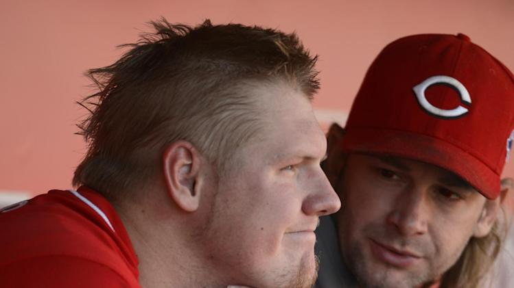 Cincinnati Reds starting pitcher Mat Latos sits in the dugout with Bronson Arroyo, right, after Latos gave up a grand slam to San Francisco Giants' Buster Posey in the fifth inning of Game 5 of the National League division baseball series, Thursday, Oct. 11, 2012, in Cincinnati. (AP Photo/Michael Keating)