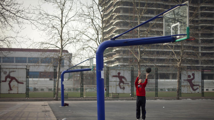 In this Saturday, Jan. 19, 2013 photo, a student plays basketball at his college's court in Beijing. Despite its formidable performance in recent Olympic Games, China has found itself in a crisis of declining fitness among its youngsters. (AP Photo/Alexander F. Yuan)