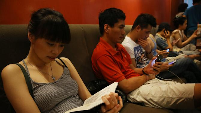 A young Vietnamese girl reads a book while other youngsters use smart phones to go online at a cafe in Ha Noi, Viet Nam Wednesday, May 14, 2013. Close to a third of Vietnam's 90 million people are online and men and women browsing phones and tablets are ubiquitous in the cafes of its towns and cities. The country's potential for growth, young population and good Internet infrastructure have made it an attractive destination for regional and international investors and startups in content provision, e-payment and other services. (AP Photo/Na Son Nguyen).