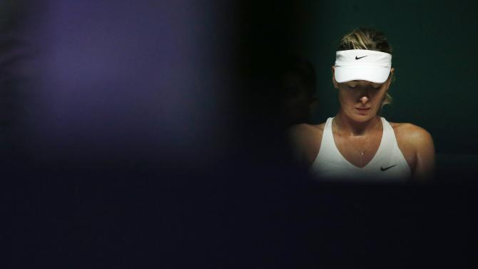 Maria Sharapova of Russia rests during sets during her WTA Finals singles tennis match against Caroline Wozniacki of Denmark at the Singapore Indoor Stadium