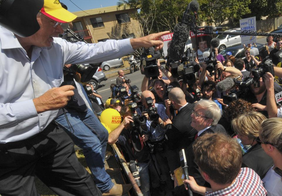 Australian Prime Minister Kevin Rudd, center, looks up at a protester, left, after casting his vote in Brisbane, Australia Saturday, Sept. 7, 2013. Australians voted Saturday in a national election that is expected to see the Labor Party ousted from government after six years in power. (AP Photo/John Pryke)