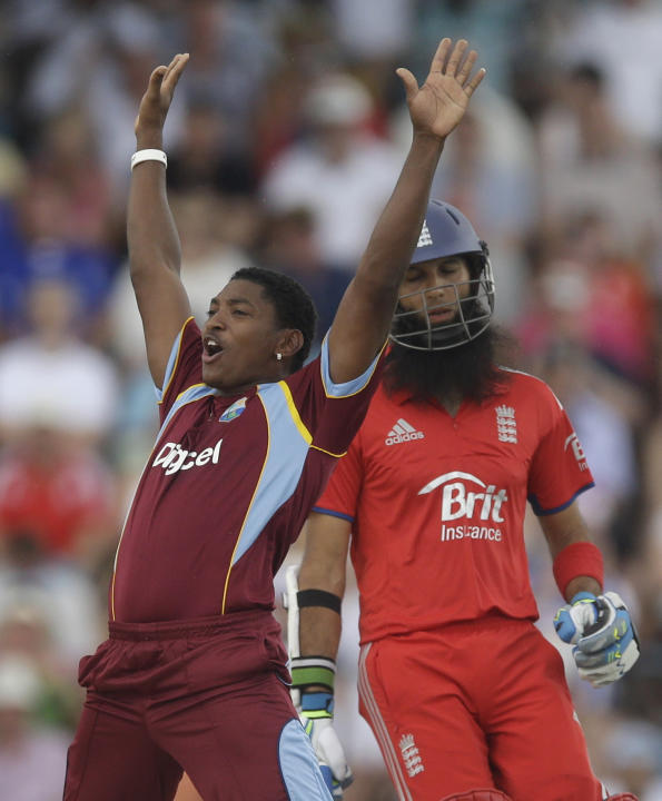 West Indies' Krishmar Santokie celebrates dismissing England's Moeen Ali, back, by LBW during their second T20 International cricket match at the Kensington Oval in Bridgetown, Barbados, Tuesd
