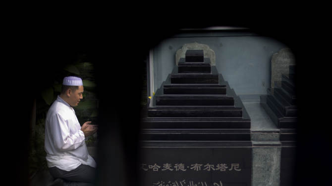 A Chinese Muslim man offers prayers at the tomb site of two former Muslim Imams during Eid al-Fitr morning prayers at the Niujie mosque, the oldest and largest mosque in Beijing, China Tuesday, July 29, 2014. Muslims in China celebrated the Eid al-Fitr on Tuesday which marks the end of the holy fasting month of Ramadan. (AP Photo/Andy Wong)