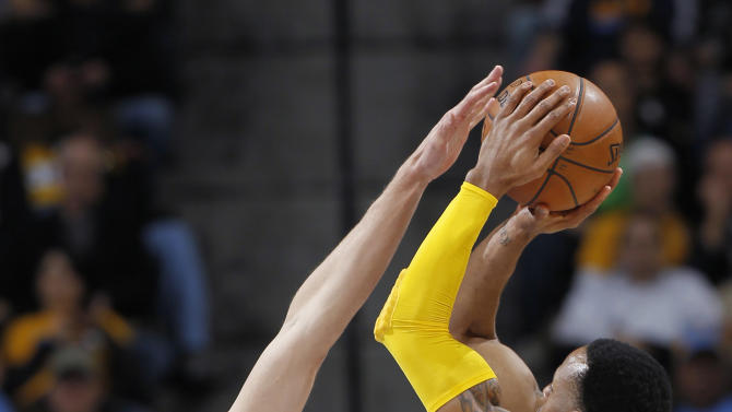 Sacramento Kings center Cole Aldrich, left, reaches up to block a shot by Denver Nuggets guard Andre Iguodala in the first quarter of an NBA basketball game in Denver on Saturday, March 23, 2013. (AP Photo/David Zalubowski)