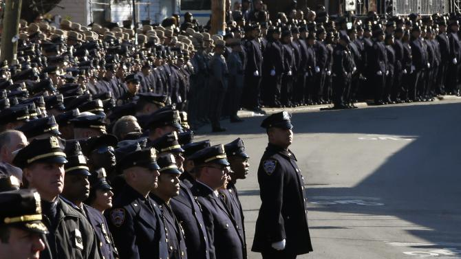 New York City police officers stand at attention in silence outside the Christ Tabernacle Church during the funeral service for slain NYPD officer Rafael Ramos in the Queens borough of New York