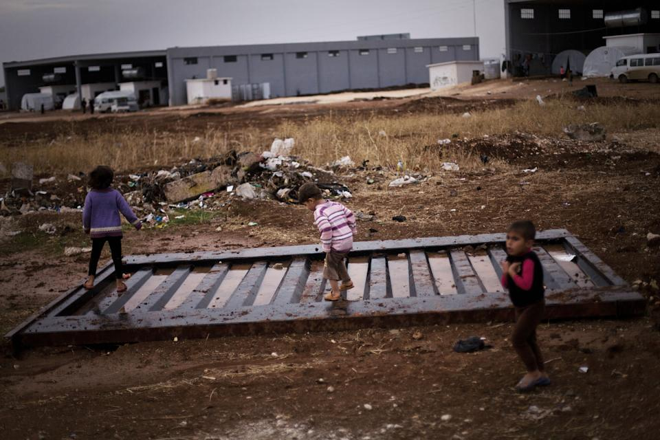 Three Syrian displaced children play in the puddles in a refugee camp near Azaz, Syria, Tuesday, Oct. 23, 2012. (AP Photo/ Manu Brabo)