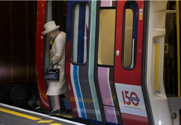 Britain's Queen Elizabeth II steps off a parked train she was shown at Baker Street underground station in London, for a visit to mark the 150th anniversary of the London Underground, Wednesday, March