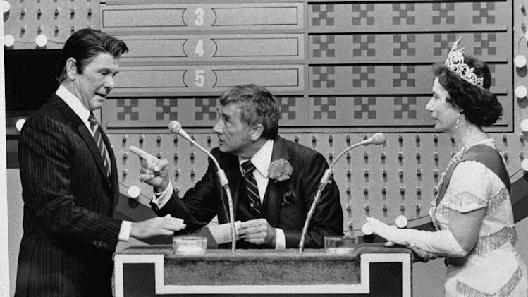 """FILE - In this Nov. 5, 1982 file photo provided by NBC-TV, """"Family Feud"""" host Richard Dawson, center, gives President Reagan, played by """"Tonight Show"""" host Johnny Carson, a chance at the big money as Queen Elizabeth (Rose Carr) readies herself at the buzzer during """"International Family Feud"""" sketch on the show in Burbank, Calif. The """"feud"""" pitted the Reagans against the Windsor family. Dawson, the wisecracking British entertainer who was among the schemers in the 1960s sitcom """"Hogan's Heroes"""" and a decade later began kissing thousands of female contestants as host of the game show """"Family Feud"""" died Saturday, June 2, 2012. He was 79. (AP Photo/NBC-TV, File)"""
