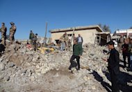 Local men and soldiers inspect the site of an explosion in Kirkuk, Iraq, on January 16, 2013