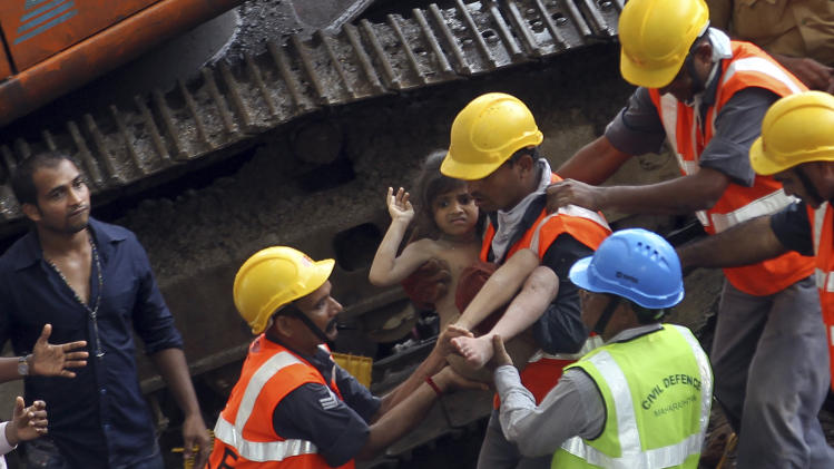 Rescue workers carry a girl out from the rubble of a building that collapsed in Mumbai, India, Friday, Sept. 27, 2013. The apartment building collapsed in India's financial capital of Mumbai early Friday, killing people and sending rescuers racing to reach dozens of people trapped in the rubble. (AP Photo/Rajanish Kakade)