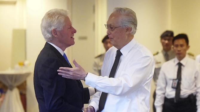 Former U.S. president Bill Clinton, left, is greeted by Singapore emeritus Senior Minister Goh Chok Tong at the state funeral for the late Lee Kuan Yew, at the University Cultural Center,  Sunday, March 29, 2015 in Singapore.  During a week of national mourning that began Monday after Lee's death at age 91, some 450,000 people queued for hours for a glimpse of Lee's coffin at Parliament House. A million people visited tribute sites at community centers across the island and leaders and dignitaries from more than two dozen countries attended the state funeral. (AP Photo/Joseph Nair)