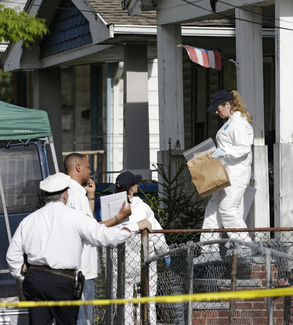 Members of the FBI evidence response team carry out evidence from a house Tuesday, May 7, 2013, where three women who vanished a decade ago were held, in Cleveland. The women were found safe Monday, and police arrested three brothers accused of holding the victims against their will. (AP Photo/Tony Dejak)