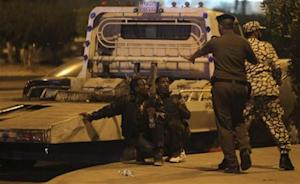 Members of Saudi security forces detain Ethiopian workers during a riot in Manfouha, southern Riyadh