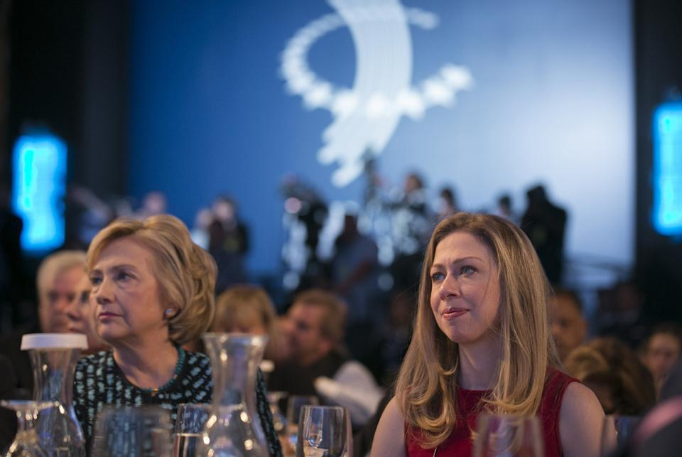 Former U.S. Secretary of State and former U.S. first lady Hillary Clinton and daughter Chelsea watch the discussions on stage at the Clinton Global Initiative 2013 in New York