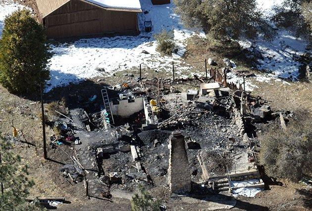 Law enforcement investigates the charred remains of a cabin Wednesday, Feb. 13, 2013. (Photo: The Sun, John Valenzuela)
