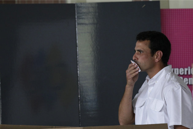 Opposition presidential candidate Henrique Capriles kisses his ballot before putting it in a box as he votes in the presidential election in Caracas, Venezuela, Sunday, Oct. 7, 2012. Capriles is running against President Hugo Chavez. (AP Photo/Ariana Cubillos)