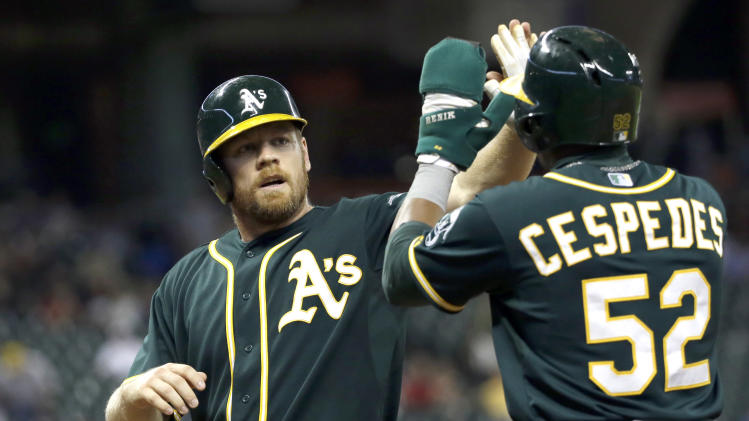 Oakland Athletics' Brandon Moss, left, and Yoenis Cespedes celebrate after scoring on Josh Donaldson's double during the ninth inning of a baseball game against the Houston Astros Tuesday, July 29, 2014, in Houston. The Athletics beat the Astros 7-4. (AP Photo/David J. Phillip)