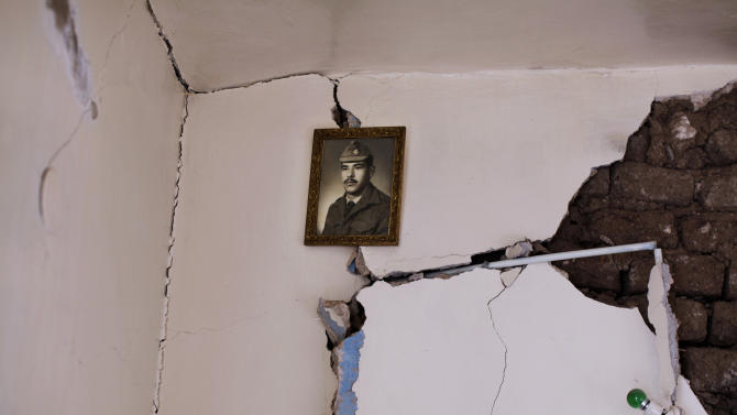 In this Friday, Aug. 31, 2012 photo, a portrait of Syrian Mahmoud Zakariya, 70, when he was a soldier, hangs on a wall inside a Syrian house, one of more than a dozen homes destroyed in a Syrian government airstrike on August 15, 2012, that killed more than 40 people, in Azaz, on the outskirts of Aleppo, Syria. Over the past week, survivors and relatives have returned daily to collect from the rubble what can be salvaged as they also relive the day of the airstrike. (AP Photo/Muhammed Muheisen)