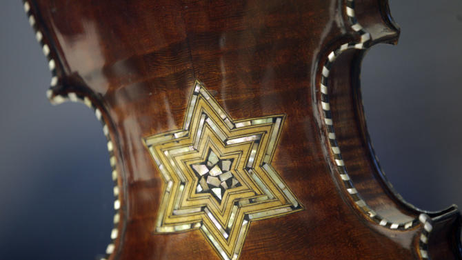In this April 9, 2012 photo, the back of a violin showing a Star of David is shown on display at the Violins of Hope exhibit at the University of North Carolina in Charlotte, N.C. Eighteen violins recovered from the Holocaust and restored by  Israeli violin maker Amnon Weinsten make their U.S. debut on Sunday, April 15. Some were played by Jewish prisoners in Nazi concentration camps, while others belonged to the Jewish Klezmer musical culture. (AP Photo/Chuck Burton)