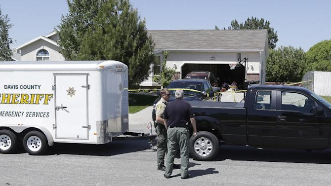 Law enforcement officials from Davis County investigate the deaths of two young boys Thursday, May 23, 2013, in West Point, Utah. A teenager was arrested Thursday in the deaths of his two younger brothers, ages 4 and 10, at the family home in a Utah subdivision of new homes and tidy lawns, police said. Davis County Sheriff Todd Richardson said authorities believe the boys died from knife wounds. It appears the 15-year-old boy acted alone, he said. (AP Photo/Rick Bowmer)