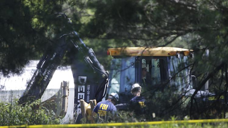 Members of an FBI evidence response team look over an area being cleared in Oakland Township, Mich., Tuesday, June 18, 2013 where officials continue the search for the remains of Teamsters union president Jimmy Hoffa, who disappeared from a Detroit-area restaurant in 1975. (AP Photo/Carlos Osorio)