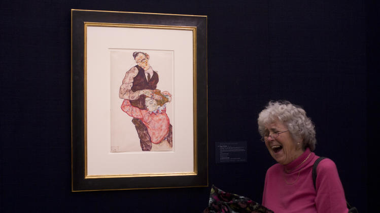 "A woman reacts to her photograph being taken next to a work on paper by Egon Schiele entitled ""Liebespaar (Selbstdarstellung mit Wally)"" ""Lovers ( Self Portrait with Wally)"" 1914-15, at Sotheby's auction house during a press preview in London, Thursday, Jan. 31, 2013.  The work is estimated to sell for some 6.5-8.5 million pounds ( US$ 10.4-13.6 million, euro 8-10.5 million) at auction in London on Feb. 5. (AP Photo/Alastair Grant)"