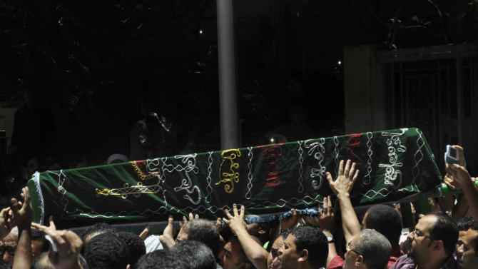 Mourners carry the coffin of Mohamed Abdel Hamid Mecca Masjid, who was killed Sunday when gunmen on a motorcycle opened fire on a protests against Egypt's Islamist President, Mohammed Morsi, in Assiut, Egypt, Monday, July 1, 2013. In the city of Assiut, a stronghold of Islamists, gunmen on a motorcycle opened fire on a protest in which tens of thousands were participating, killing one person, wounding several others and sending the crowd running. (AP Photo/Mamdouh Thabet)