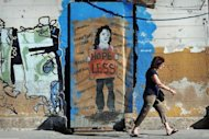 <p>A woman walks by graffiti on a wall in Athens on June 14. Spain was thrown back onto the front line of the eurozone debt crisis on Monday as its long-term borrowing rate shot above seven percent, dashing hopes for a respite after the Greek election.</p>