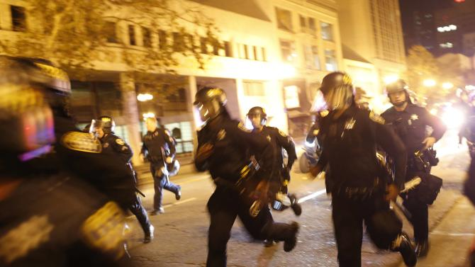 Police officers run towards protesters after a demonstration turned violent in Oakland
