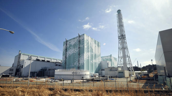 """In this photo taken Tuesday, Feb. 28, 2012, reactor buildings of Unit 6, left in center, and Unit 5, right in center, at Tokyo Electric Power Co.'s tsunami-crippled Fukushima Dai-ichi nuclear power plant is seen through a bus window in Okuma town, Fukushima prefecture, northeastern Japan. Right after three reactors of the plant sank into meltdowns, the government vowed to crack down on the cozy relations between the nuclear industry and its regulators. However, Japanese regulators have responded more slowly than their American counterparts did after the accident at Three Mile Island in 1979. Only two plants - one of them is Fukushima Dai-ichi - have built up seawalls since the meltdowns. """"All we can do is pray a tsunami won't come,"""" said Hideyuki Ban, who heads the anti-nuclear research group Citizens' Nuclear Information Center and sits on a government panel on atomic energy policy. (AP Photo/Kimimasa Mayama, Pool)"""