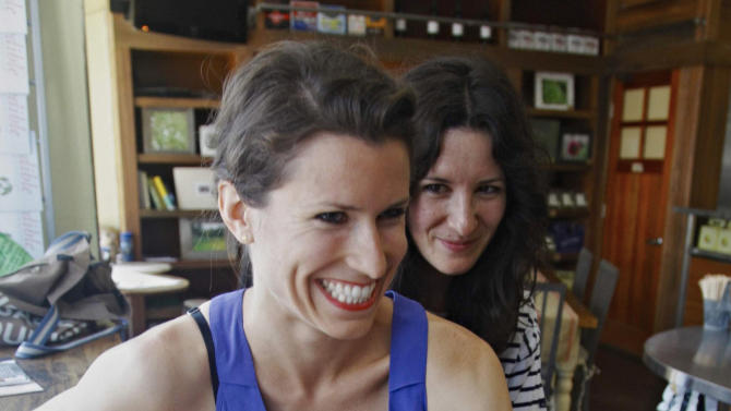 In this July 19, 2011 photo, Tiffany Peckosh, 31, left, and Meredith Soffrin, 30, react during an interview in New York. Peckosh and Soffrin plan to marry Sunday, July 24, under New York's new gay marriage law. (AP Photo/Bebeto Matthews)