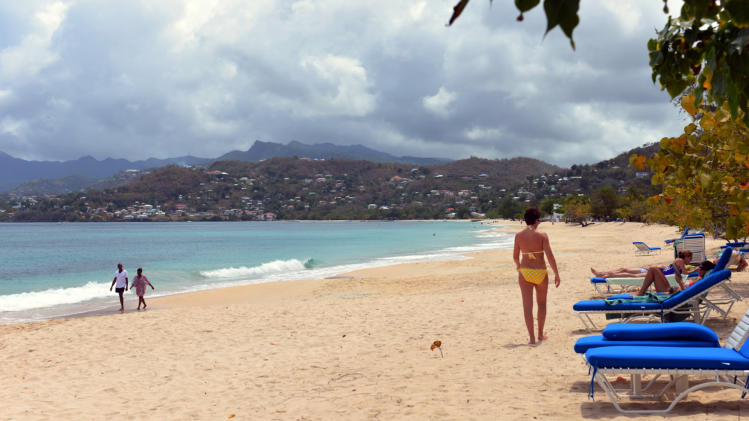 In this April 25, 2013 photo, tourists walk on the white sand of the Grand Anse Beach, Grenada. The people along this vulnerable stretch of eastern Grenada have been watching the sea eat away at their shoreline in recent decades, a result of destructive practices such as sand mining and a ferocious storm surge made worse by climate change, according to researchers with the U.S.-based Nature Conservancy, who have helped locals map the extent of coastal erosion. (AP Photo/David McFadden)