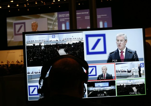 A technician watches a monitor showing Juergen Fitschen, Co-CEO of Deutsche Bank AG as he speaks during a shareholders meeting in Frankfurt