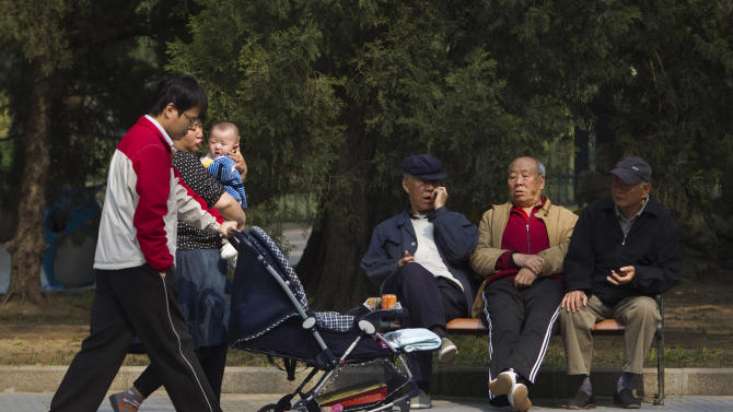 "FILE - In this April 28, 2011 file photo, elderly men rest on a bench as a family with their new born baby walk past at a park in Beijing, China. Visit your parents. That's an order. So says China, whose national legislature on Friday, Dec. 28, 2012 amended its law on the elderly to require that adult children visit their aged parents ""often"" - or risk being sued by them. (AP Photo/Alexander F. Yuan, File)"