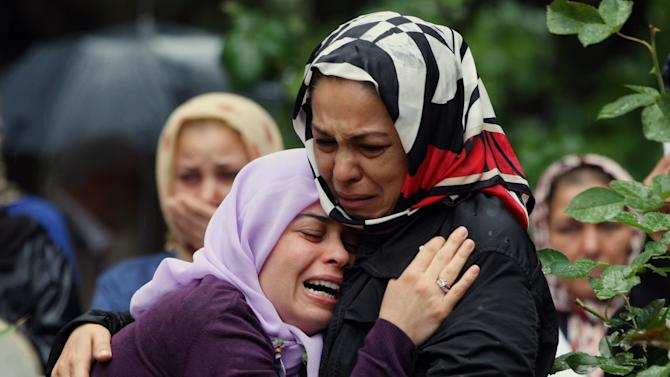 Mourning relatives cry during the burial for one of the 46 victims killed in Saturday explosions in Reyhanli, near Turkey's border with Syria, Sunday, May 12, 2013. The bombings on Saturday marked the biggest incident of cross-border violence since the start of Syria's bloody civil war and has the raised fear of Turkey being pulled deeper into the conflict.(AP Photo/Burhan Ozbilici)