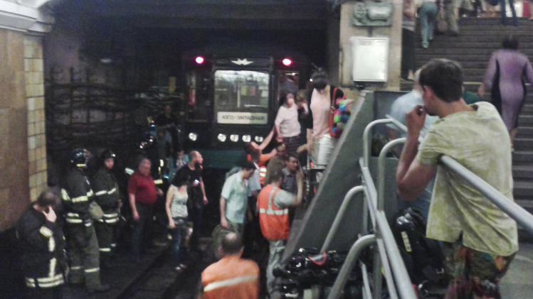 In this image made by a mobile phone camera, people leave a subway station in downtown Moscow on Monday, June 5, 2013. A rush-hour fire in Moscow's subway injured dozens of people, forced the evacuation of thousands of commuters and closed parts of the network on Wednesday, authorities said. As firefighters were putting out the fire, authorities closed one of the subway lines that cuts through central Moscow. Eyewitnesses say central Moscow streets were thronged with crowds who ended up walking to work. (AP Photo/Echo Moskvy, Andrey Poznyakov)